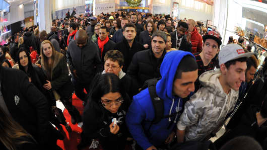 People rush into Macy's department store as they open at midnight (0500 GMT) on November 23, 2012 in New York to start the stores' 'Black Friday' shopping weekend.