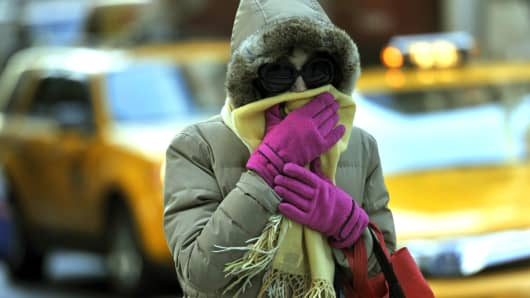 A woman braces from the cold during the morning commute in New York City November 25, 2013 as temperatures dropped into the lower 30's(F).