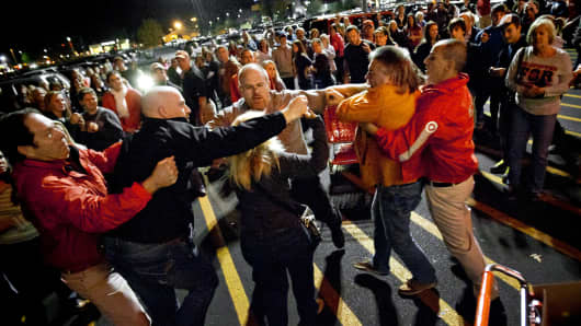 A crowd gathers as security guards break up a fight between shoppers waiting in line just as the doors open for Black Friday shopping at Target, Thursday, Nov. 22, 2012, in Bowling Green, Ky.