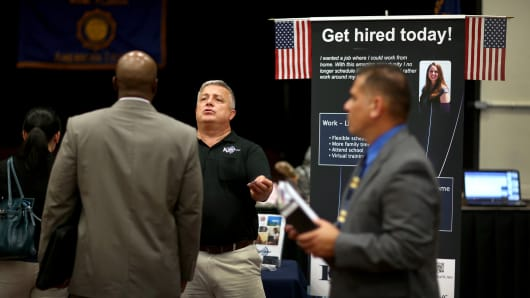 Hans Kahl (C) speaks with prospective employees as he recruits for Kahl Center during a job fair in Miami.