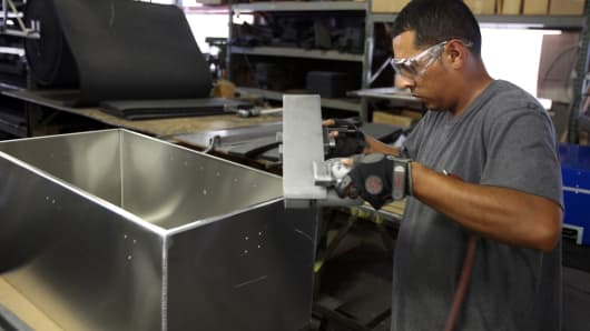 A worker sands an aluminum case at the Aluminum Case Company, a division of MFZ Ventures, Inc.