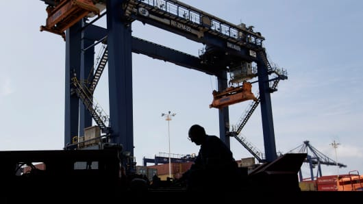 A worker and crane at a port in Mexico.