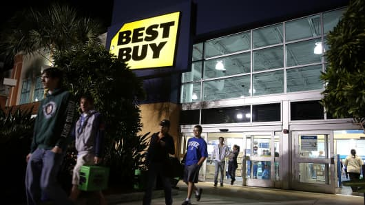 Black Friday shoppers carry away discounted items from a Best Buy store which opened its doors at 6 p.m. on Thanksgiving Day in Naples, Fla.