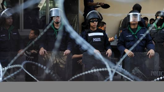 Thai policemen stand guard behind barbed wire at the National Police Headquarters in Bangkok on December 1, 2013.