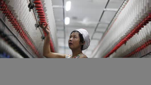 An employee works in a textile factory in Huaibei, east China's Anhui province on October 24, 2013.