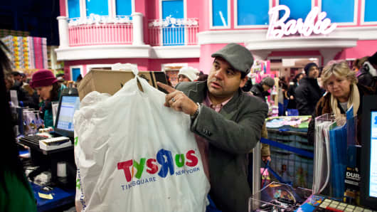 A customer pays for his items at Toys'R'Us in Times Square on November 28, 2013 in New York City.