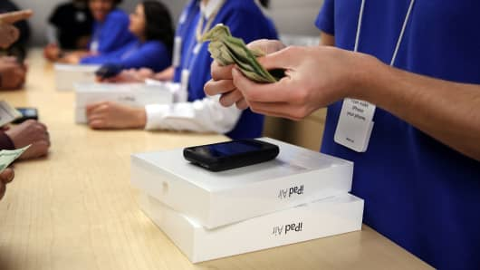 People buy the new Apple iPad Air at the Apple Store in New York City.