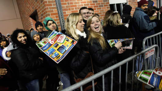 Customers wait in line to enter a Wal-Mart on Thanksgiving Day in Troy, Mich.
