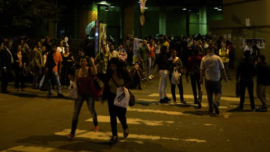 People stand outside a subway station during a general blackout in Caracas on December 2, 2013.