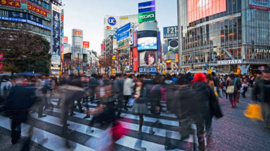 Shibuya Crossing, crowds of people crossing the intersection in the center of Shibuya in Tokyo.