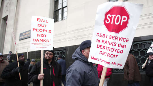 People protest outside the U.S. Courthouse where federal bankruptcy Judge Steven Rhodes is to rule on Detroit's Chapter 9 bankruptcy eligibility December 3, 2013 in Detroit, Michigan.