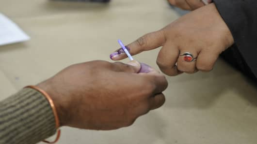 Woman gets her finger marked with ink after casting her vote for Delhi Assembly elections, India, December 4, 2013