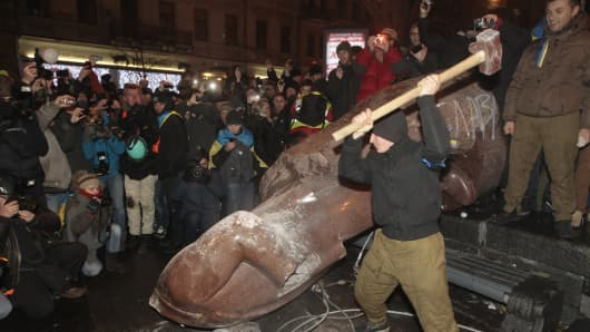 An anti-government protester beats the statue of Vladimir Lenin with a sledgehammer in Kiev, Ukraine, Sunday, Dec. 8, 2013.
