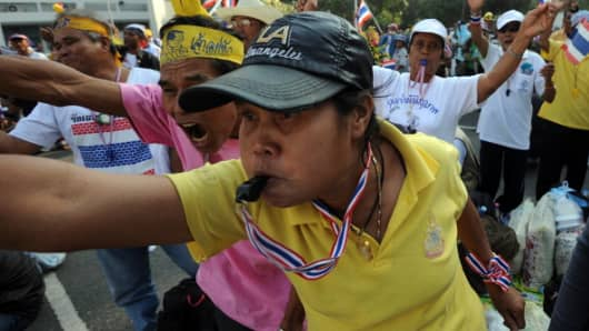 Anti-government protesters shout slogans and blow whistles as they prepare for a march to the Government House in Bangkok on December 9, 2013.
