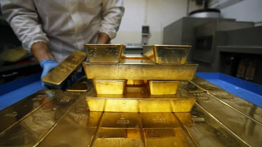 An employee stacks gold bars onto a cart inside the precious metals refinery plant.