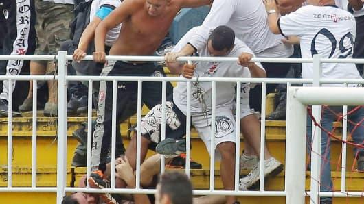 Fans of Rio de Janeiro's Vasco da Gama attack a fan of Parana's Atletico PR, during a Brazilian Championship football match in Joinville, Santa Catarina, on December 8, 2013.