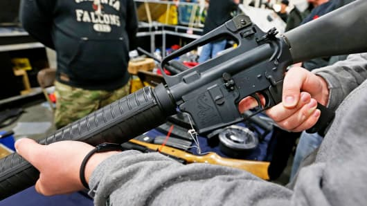 A man holds a Bushmaster AR-15 Model A2 semi-automatic assault rifle at the Rocky Mountain Gun Show in Sandy, Utah.