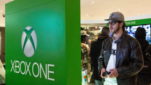 A man uses an XBox One while waiting to buy a console from a Microsoft pop-up shop at the Time Warner Center in New York.