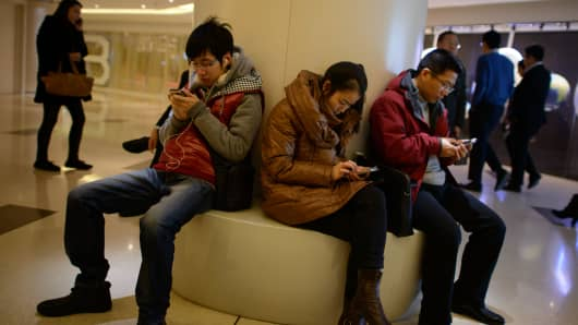 People use their mobile phones as they sit inside a shopping mall in Beijing, November 27 2013.