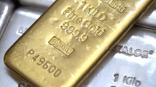 A one kilogram gold bar sits on top of silver bars.