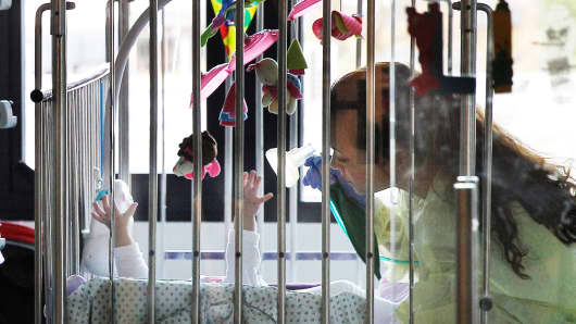 A nurse helps a baby with a respiratory mask, at the intensive care unit of the Queen Fabiola Children's Hospital in Brussels, Belgium.