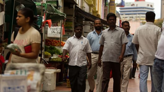 Foreign workers walk around Little India, Singapore the day after the riot on 8 December 2013
