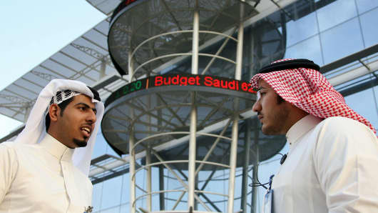 Saudi men chat outside the Saudi Stock Exchange or Tadawul in Riyadh.