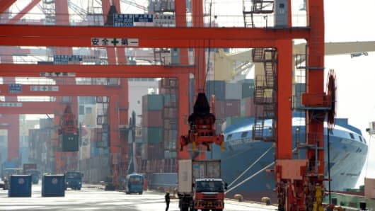 Containers are loaded onto a cargo ship at the pier in Tokyo port on January 24, 2013