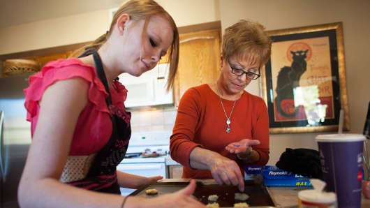 Leslie Davis helps granddaughter Hunter Hill, 15, bake holiday cookies at Davis' home in Mesa, Ariz.