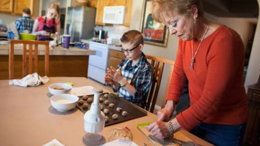 Grandparent Leslie Davis helps her grandchildren bake holiday cookies at her home in Mesa, Ariz.