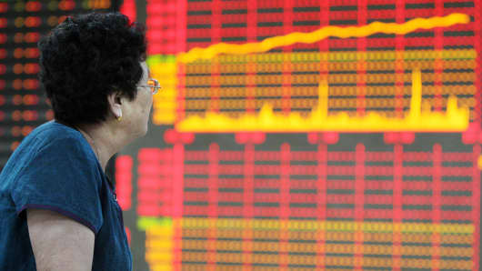 A woman watches the electronic board at a stock exchange hall in Huaibei, China.