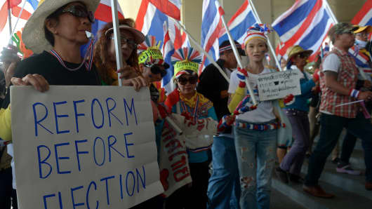 Thai anti-government protesters hold placards during a rally at the Election Commission headquarters in Bangkok on December 17, 2013.
