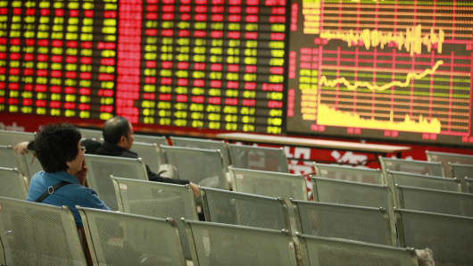 Investors watch the electronic board at a stock exchange hall in Huaibei, China.