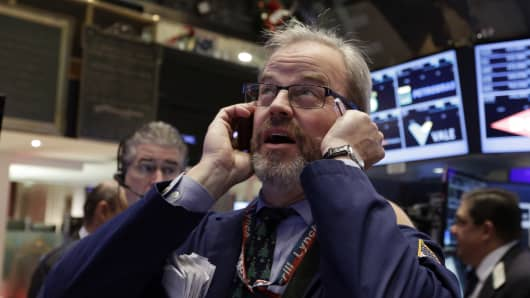 A trader uses his mobile phone as he works on the floor of the New York Stock Exchange on Wednesday.