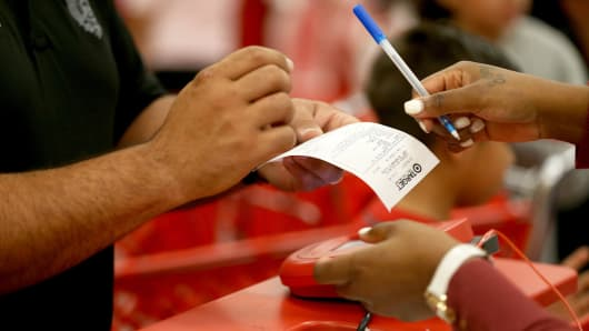 A Target customer prepares to sign a credit card slip.