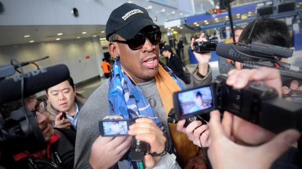 Former US NBA basketball player Dennis Rodman (C) speaks to members of the media as he makes his way through Beijing's international airport on December 19, 2013. Rodman is on a visit to North Korea from December 19 to 23.