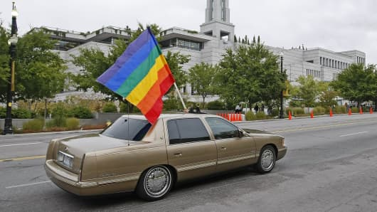 In this file photo, A car flies the gay pride flag in protest past the Mormon Conference center in Salt Lake City, Utah.