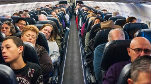 Passengers aboard an Allegiant Airlines flight en route from Las Vegas to Colorado Springs, Colo., Dec. 19, 2013.