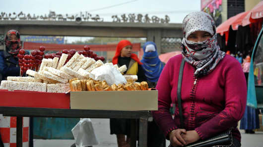 This picture taken on November 6, 2013 shows Uighur women shopping at a bazaar in Hotan, farwest China's Xinjiang region.