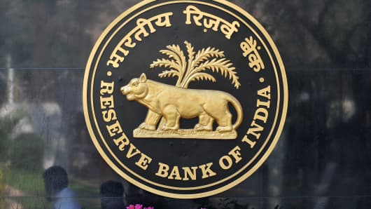 Passers by are reflected on the logo of the Reserve Bank of India outside its headquarters in Mumbai on January 29, 2010.