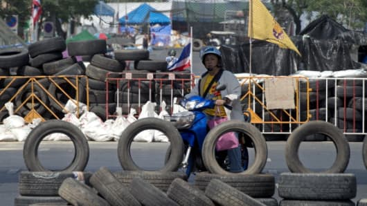 Thai anti government protester rides past barricades during a rally at Government House in Bangkok on January 2, 2014. T