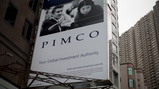 A Pacific Investment Management Company advertisement is displayed on a building in Hong Kong, China.