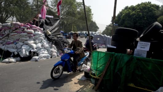 Thai anti government protesters ride motorcycle past barricades as they rally at Government House in Bangkok on January 2, 2014.
