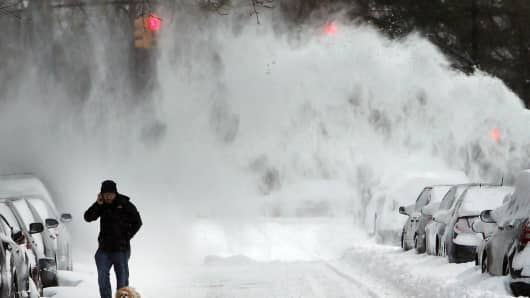 A man and his dog contend with blowing snow in Brooklyn following a snow storm that left up to 8 inches of snow on January 3, 2014 in New York.