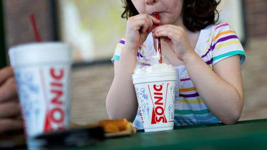 A customer sips a vanilla milkshake at a Sonic drive-in restaurant in Normal, Illinois.