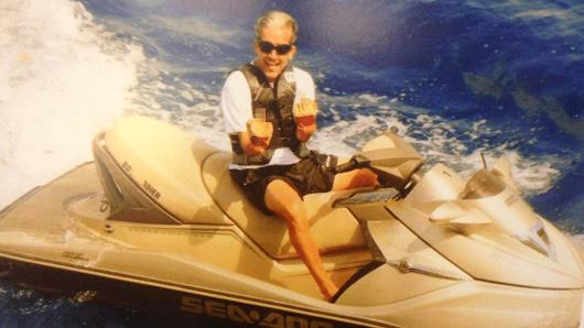 Glenn Lieberman, a suspect in a wide-ranging disability scam, sits on a wave runner, with both middle fingers hoisted. Prosecutors say he fraudulently pocketed more than $175,000.