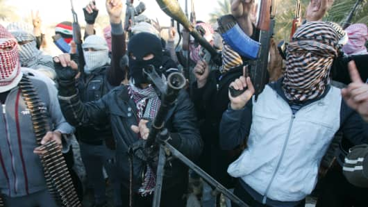 Gunmen chant slogans against Iraq's Shiite-led government and demand that the Iraqi army stay out of Fallujah, Jan. 7, 2014.