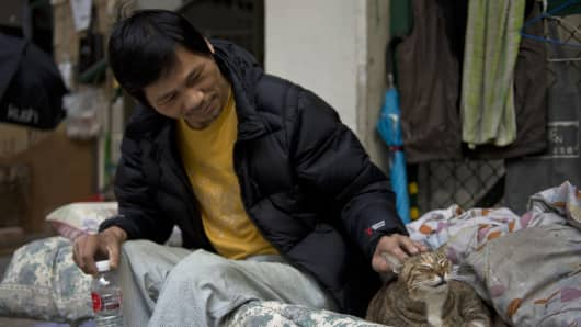 A homeless man strokes his pet cat on his bed under a walkway in Hong Kong on January, 2, 2014.