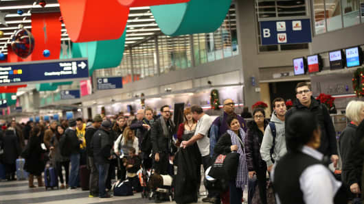Travelers wait in line to check-in for flights at O'Hare International Airport.