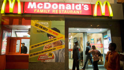 A security guard opens the door for customers at McDonalds in New Delhi, India.
